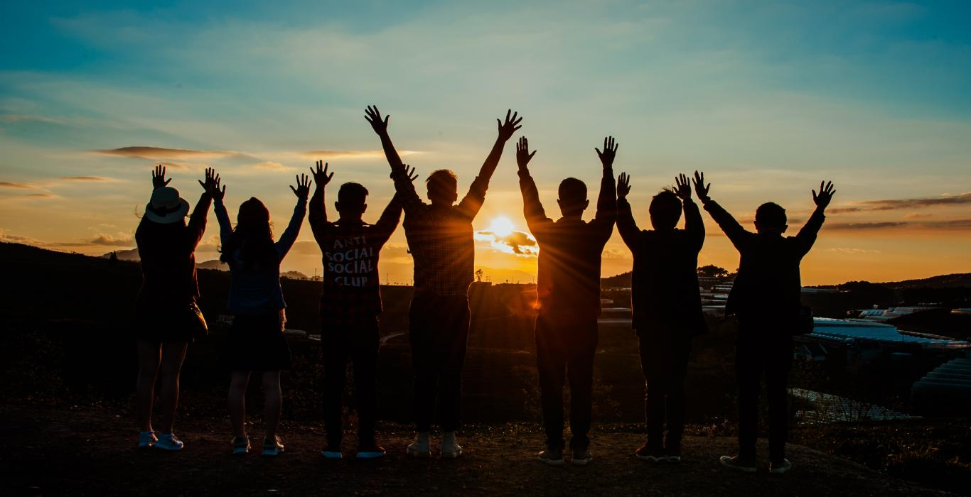 Silhouette of a group of people with their arms raised looking at the sunset